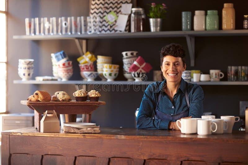 Porträt des weiblichen Kaffeestube-Inhabers, der hinter Zähler steht stockfotografie