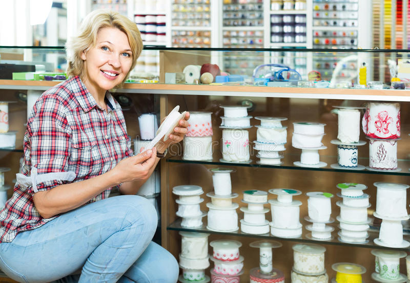Porträt des weiblichen Kunden stehend nahe bei verschiedenen Bändern für lizenzfreie stockbilder