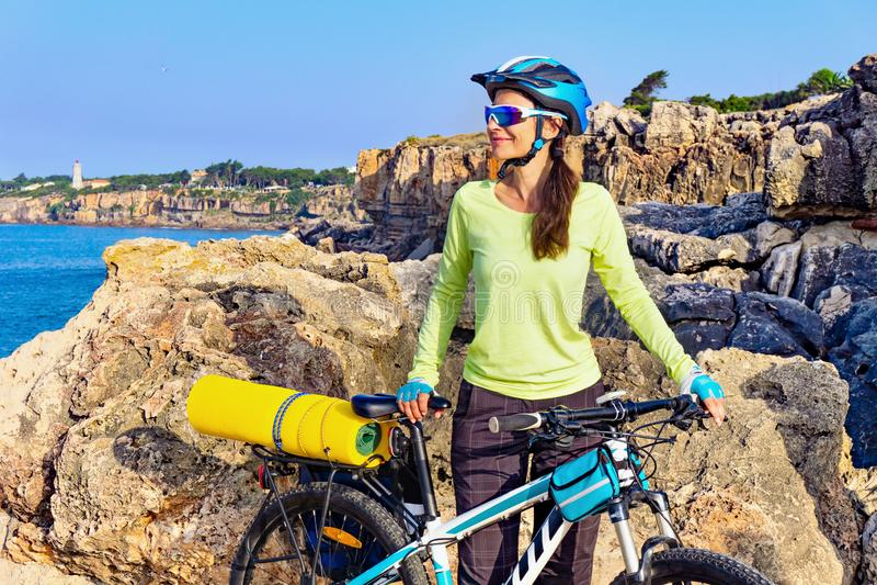 Porträt des weiblichen touristischen Radfahrers auf dem felsigen Ufer auf dem Leuchtturmhintergrund lizenzfreies stockfoto