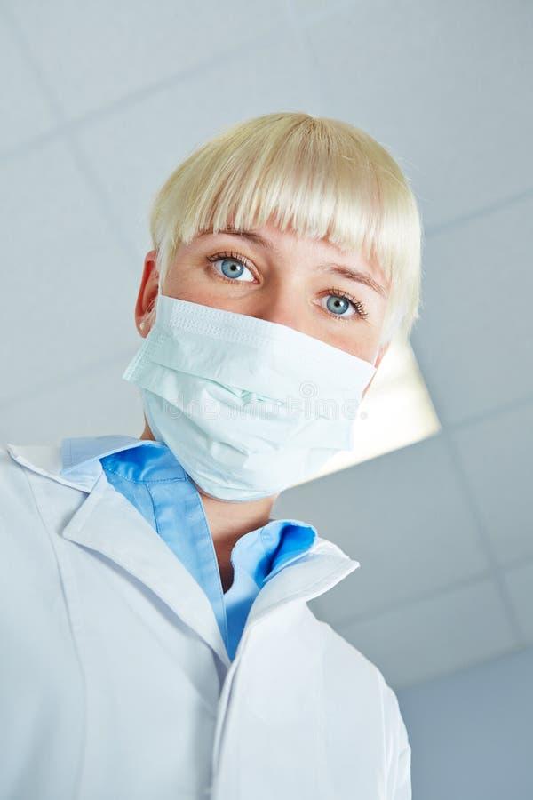 Porträt des weiblichen Zahnarztes mit chirurgischer Maske stockbild