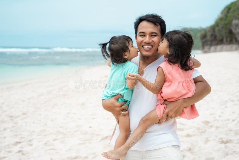 Porträt ein Vater trägt seine Tochter zwei auf dem Strand lizenzfreies stockfoto