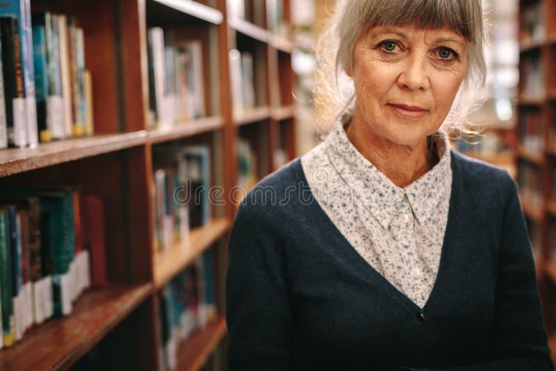 Porträt einer älteren Frau, die in einer Bibliothek steht lizenzfreie stockfotografie