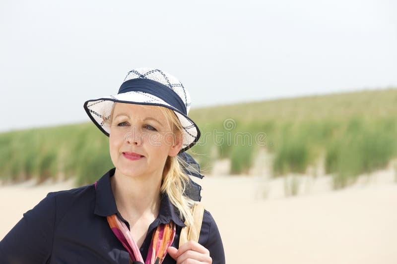 Porträt einer älteren Frau, die am Strand mit Hut steht stockfoto