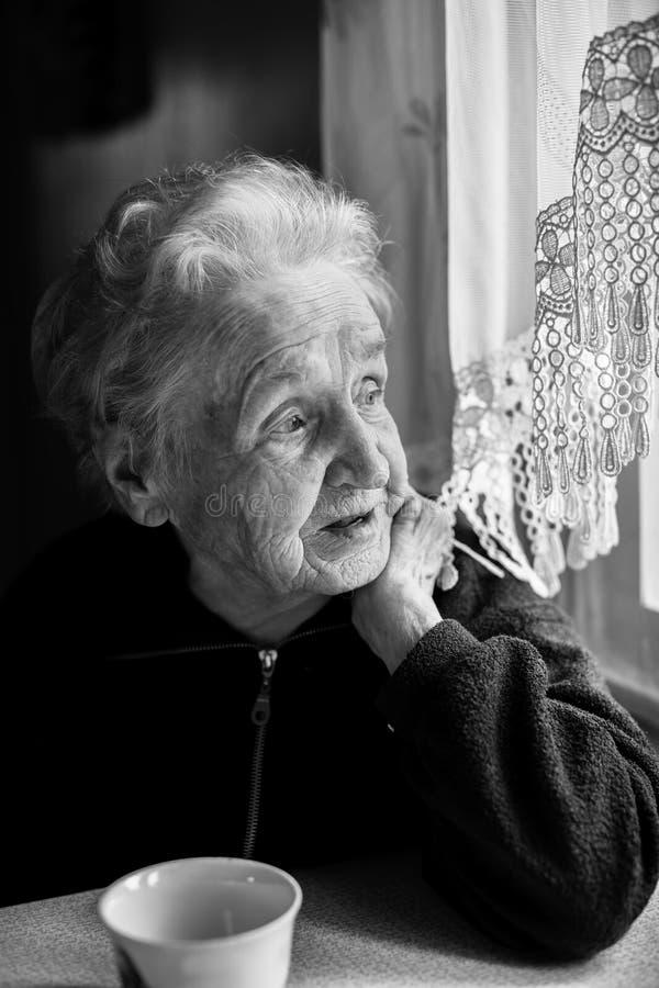 Porträt einer älteren Frau mit Tee an einem Tisch nahe dem Fenster lizenzfreies stockbild
