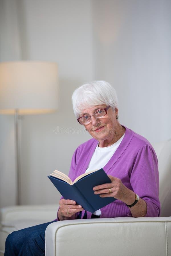 Porträt einer älteren Frau zu Hause unter Verwendung eines Buches lizenzfreie stockfotos