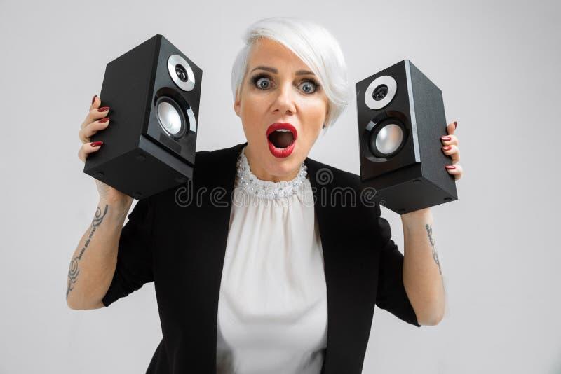 Porträt einer überzeugten Dame in einer Klage mit Sprechern in ihren Händen lokalisiert auf einem hellen Hintergrund lizenzfreies stockfoto