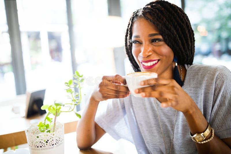 Porträt einer Afroamerikanerfrau, die am Café mit Kaffee sich entspannt lizenzfreies stockfoto