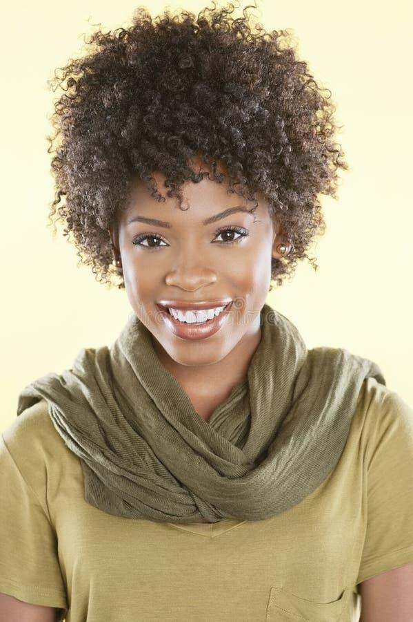 Porträt einer Afroamerikanerfrau, die mit einer Stola rund ihr Hals über farbigem Hintergrund lächelt stockfotos