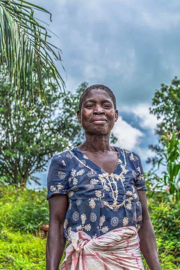 Porträt einer angolanischen Frau, gekleidet in den einfachen Roben stockfotografie