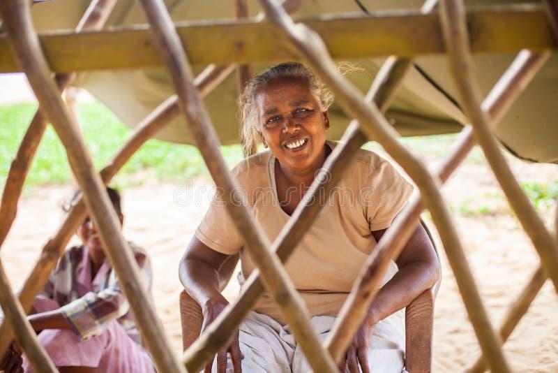 Porträt einer armen, älteren indischen Frau hinter einem Zaun in Form eines Gitters lizenzfreies stockbild