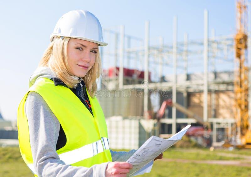 Porträt einer attraktiven Arbeitnehmerin auf einer Baustelle stockfoto