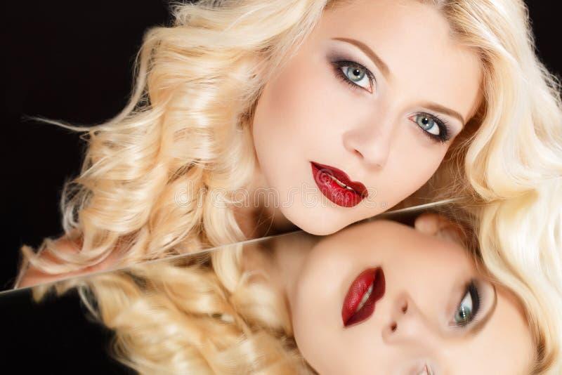 Porträt einer attraktiven blonden Frau mit dem langen gelockten Haar, lokalisiert auf schwarzer Atelieraufnahme stockfotos