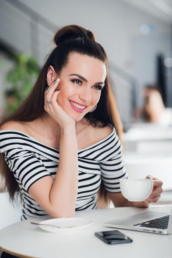 Porträt einer attraktiven erwachsenen Frau mit dem perfekten Lächeln, das einen Tasse Kaffee hält und weg glücklich schaut stockfotos