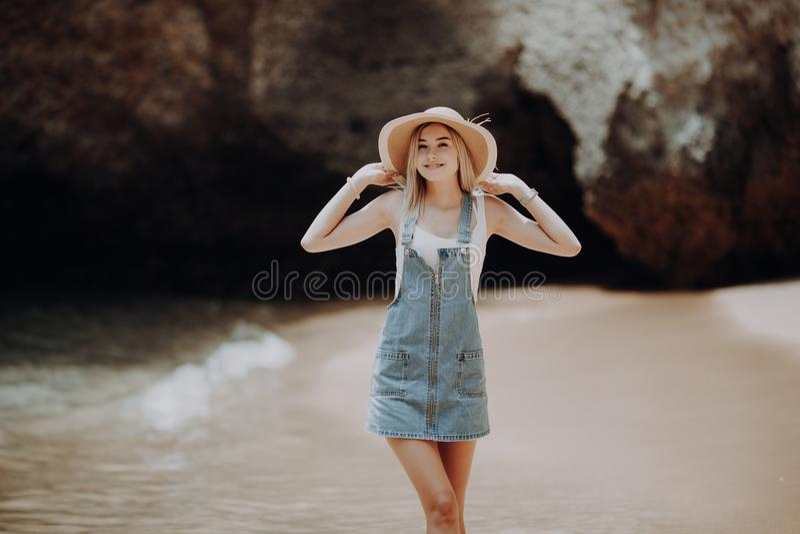 Porträt einer attraktiven Frau, die barfuß auf den Strand in den Strohhut und in Sonnenbrille tragen zufällige Kleidung geht stockfotografie