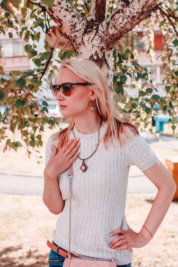 Porträt einer attraktiven jungen Frau in der Sonnenbrille, die auf der Straße aufwirft lizenzfreie stockfotos