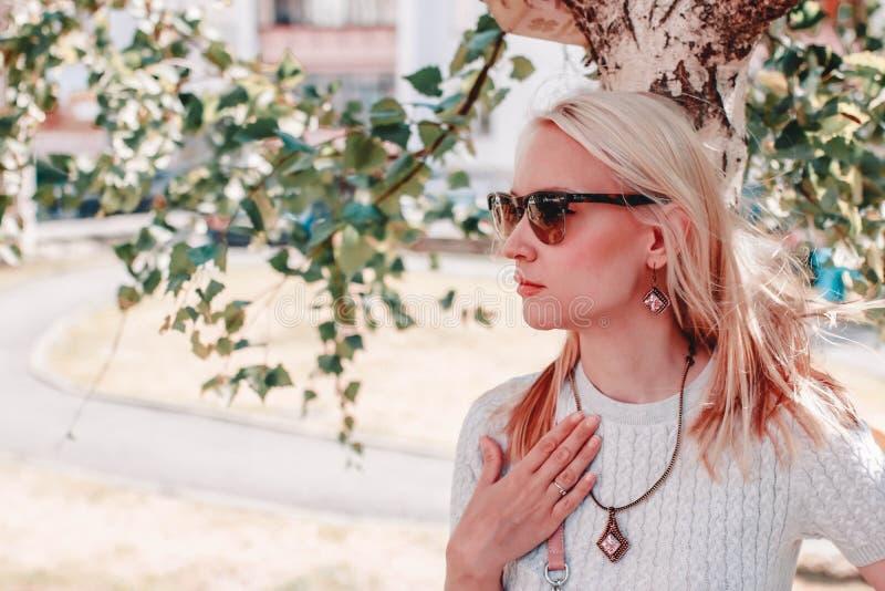 Porträt einer attraktiven jungen Frau in der Sonnenbrille, die auf der Straße aufwirft lizenzfreie stockbilder