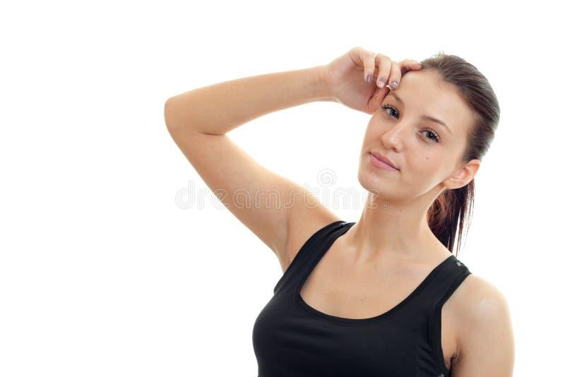 Porträt einer attraktiven jungen Frau in einem schwarzen T-Shirt, das Hand nahe dem Gesicht lächelt und hält stockfotografie