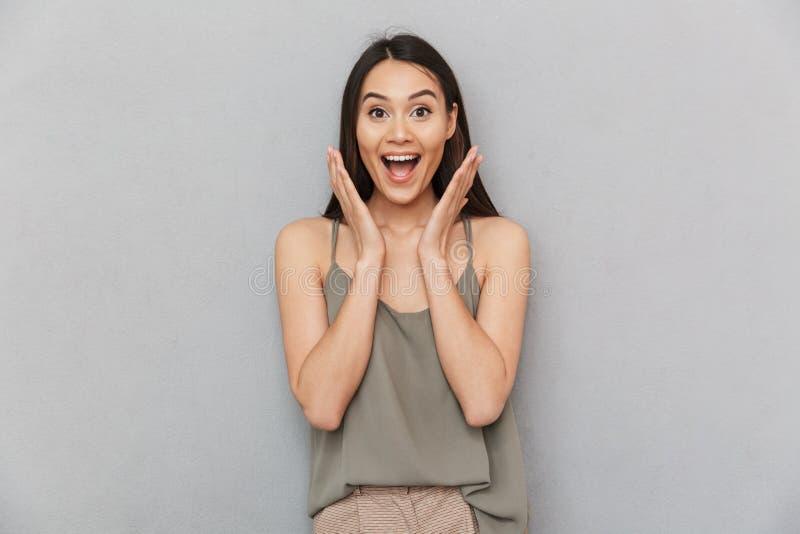 Porträt einer aufgeregten asiatischen Frau, die Kamera betrachtet lizenzfreies stockbild