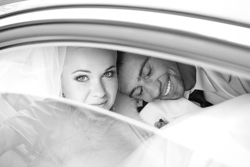 Porträt einer aufgeregten Bräutigamumarmung seine Braut im Auto lizenzfreies stockfoto