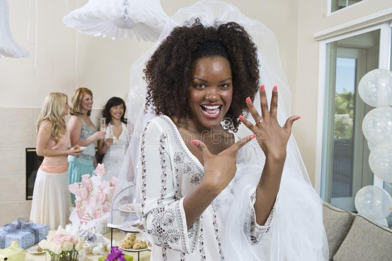 Porträt einer aufgeregten Braut, die ihren Verlobungsring zeigt stockbild