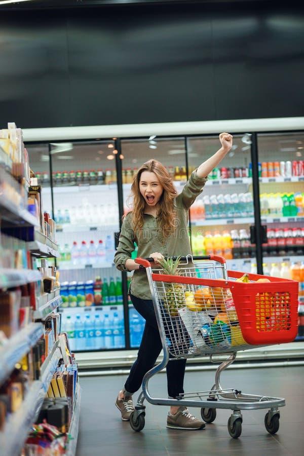 Porträt einer aufgeregten jungen zufälligen Frau, die Einkauf tut lizenzfreie stockfotos