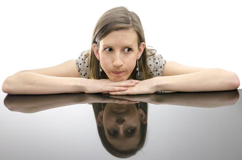 Besorgte Frau, die auf einer Tabelle sich lehnt stockfotos
