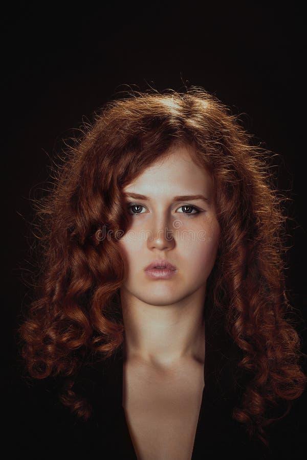 Porträt einer bezaubernden jungen Frau auf dunklem Hintergrund stockfotografie