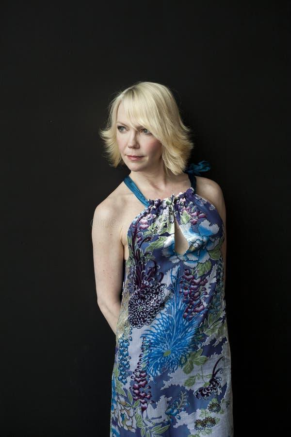 Blonde Frau mit schönen blauen Augen auf schwarzem Hintergrund lizenzfreie stockbilder