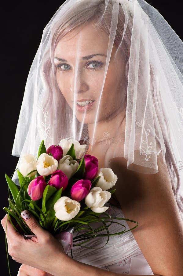 Porträt einer Braut mit einem Blumenstrauß von Tulpen stockbild