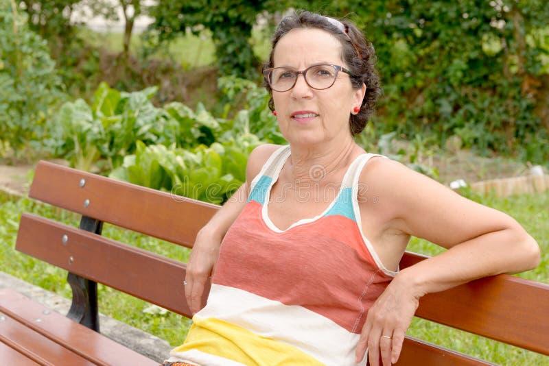 Porträt einer Brunettefrau von mittlerem Alter mit Brillen, outdoo lizenzfreies stockbild