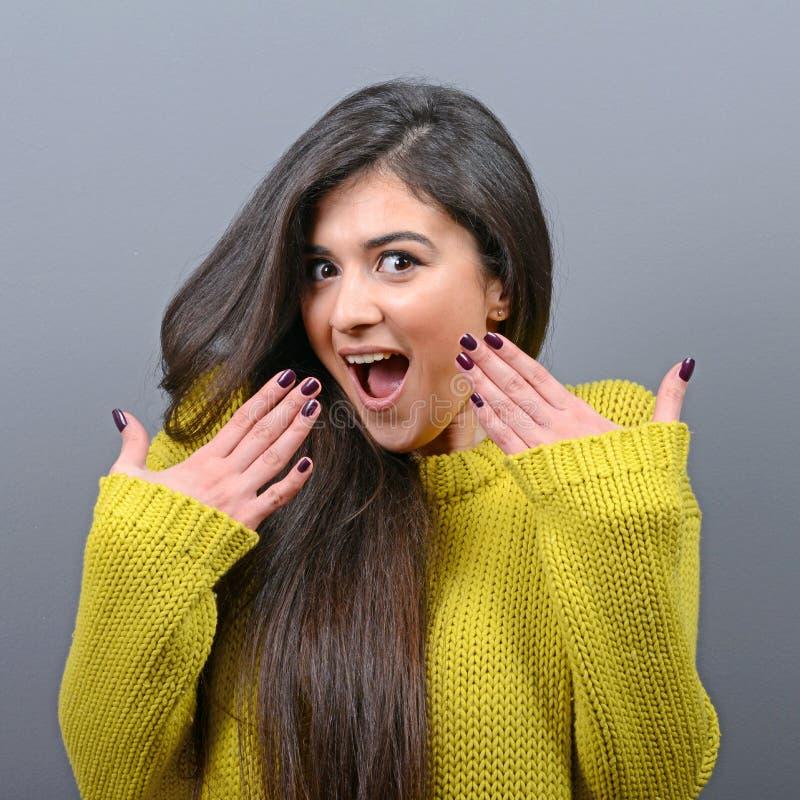 Porträt einer ekstatischen Frau mit den verbreiteten Händen gegen grauen Hintergrund stockfoto