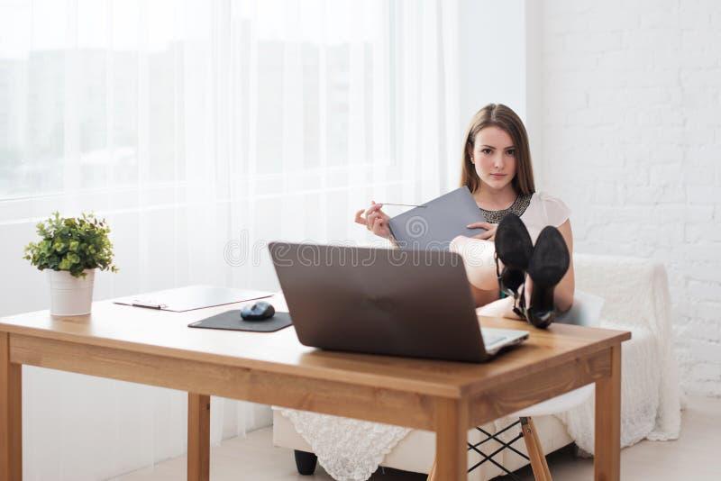 Porträt einer entspannten jungen Geschäftsfrau, die mit den Beinen auf Schreibtisch im Büro sitzt lizenzfreie stockbilder