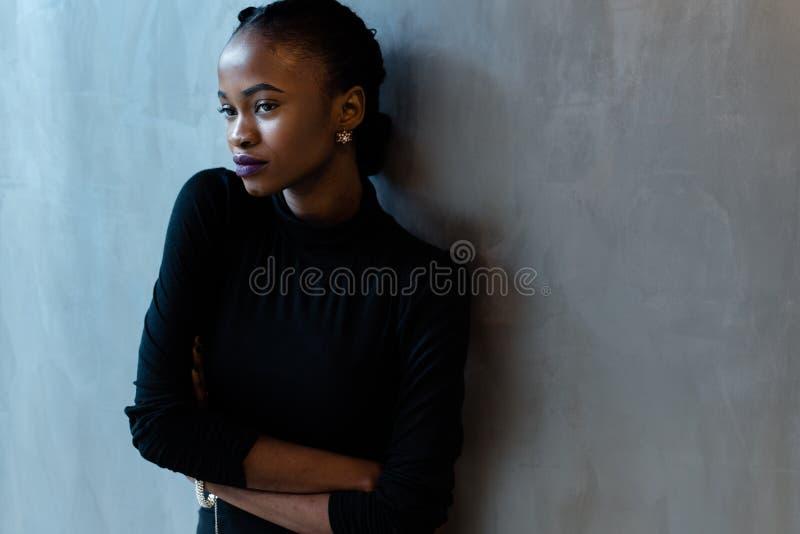 Porträt einer ernsten afrikanischen oder schwarzen amerikanischen Frau mit den Armen faltete Stellung über grauem Hintergrund und lizenzfreies stockfoto