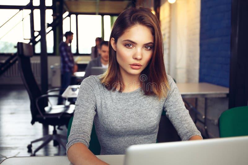 Porträt einer ernsten Geschäftsfrau, die Laptop im Büro verwendet lizenzfreie stockfotos