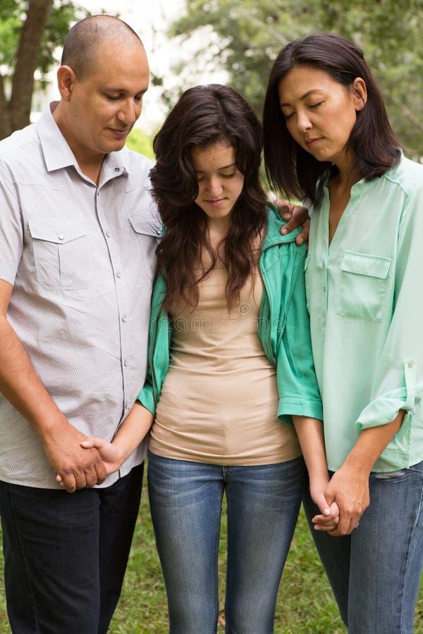 Porträt einer Familie, die mit ihrer Tochter betet stockfoto