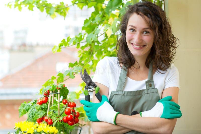 Porträt einer Frau auf ihrem Stadtgartenbalkon - Natur und Stadt lizenzfreie stockfotos
