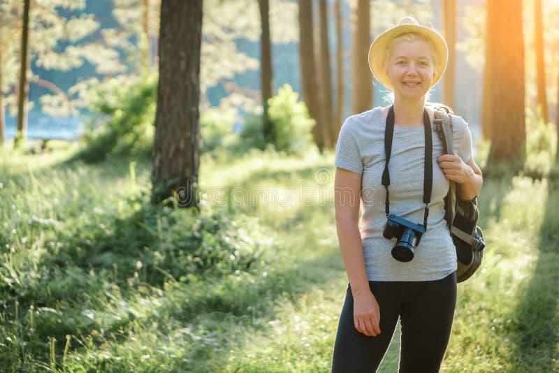 Porträt einer Frau, die in den Wald mit einer Kamera reist lizenzfreie stockfotografie