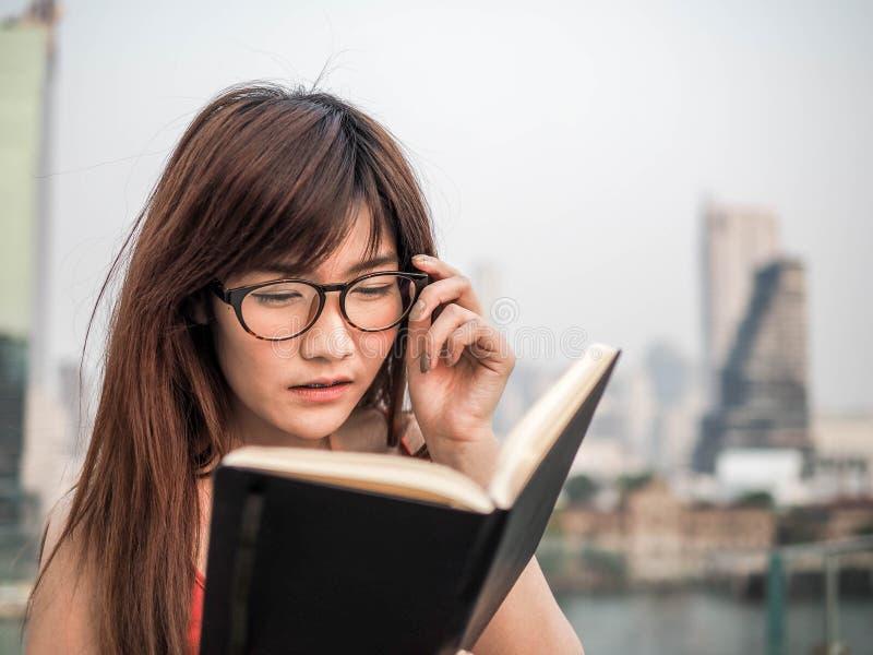 Porträt einer Frau, die ein Buch mit Gläsern liest lizenzfreie stockfotos