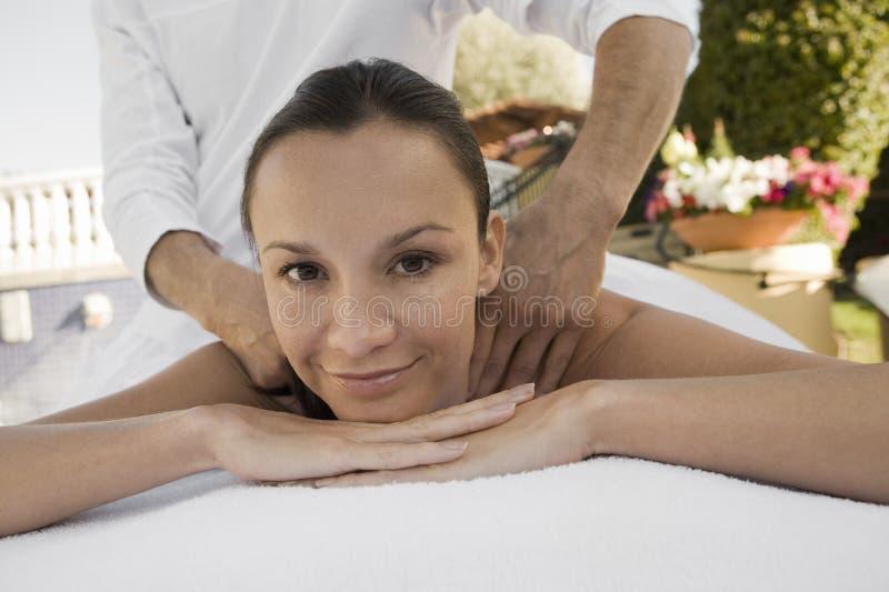Porträt einer Frau, die Schulter-Massage empfängt stockbild