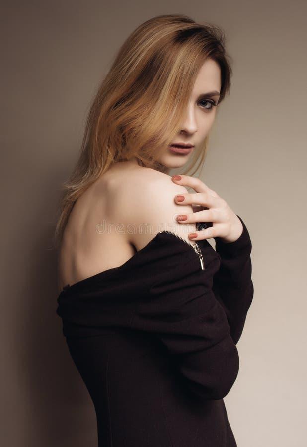 Porträt einer Frau in einem schwarzen Kleid steht seitlich rührend die offene Schulter lizenzfreies stockfoto