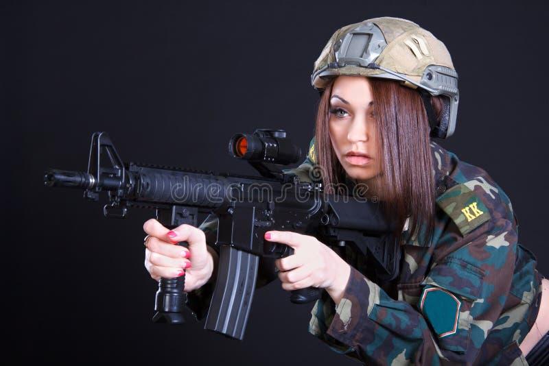 Porträt einer Frau in einer Militäruniform mit einem Sturmgewehr lizenzfreies stockfoto