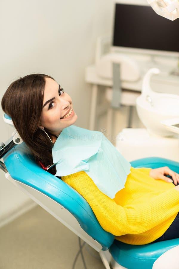 Porträt einer Frau mit dem toothy Lächeln, das am zahnmedizinischen Stuhl im zahnmedizinischen Büro sitzt lizenzfreies stockbild