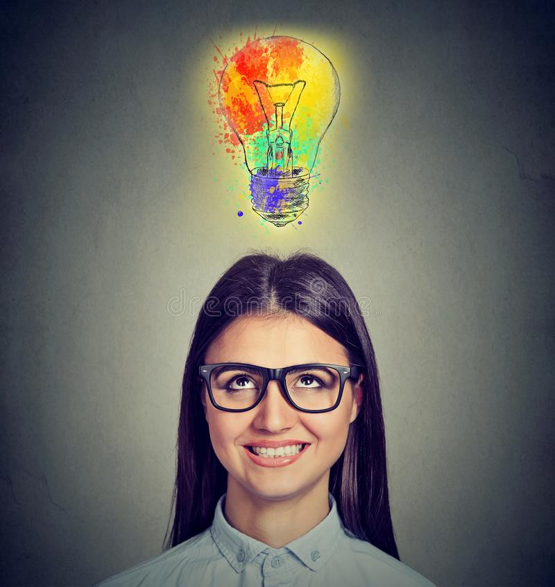 Porträt einer Frau mit den Gläsern und kreativer Idee, die oben bunter Glühlampe betrachten stockfotos