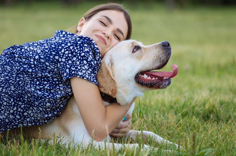 Porträt einer Frau mit ihrem schönen Hund, der draußen liegt stockbilder