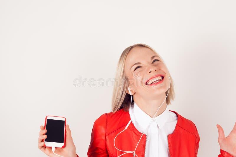 Porträt einer Frau mit Kopfhörern und Handy in der Hand in der roten Jacke auf weißem Hintergrund lizenzfreies stockfoto