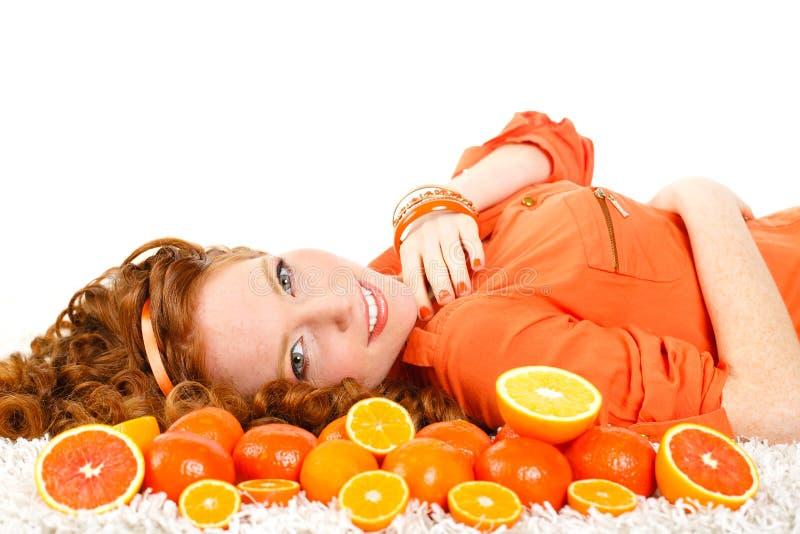Porträt einer Frau mit Orangen auf Weiß stockbilder