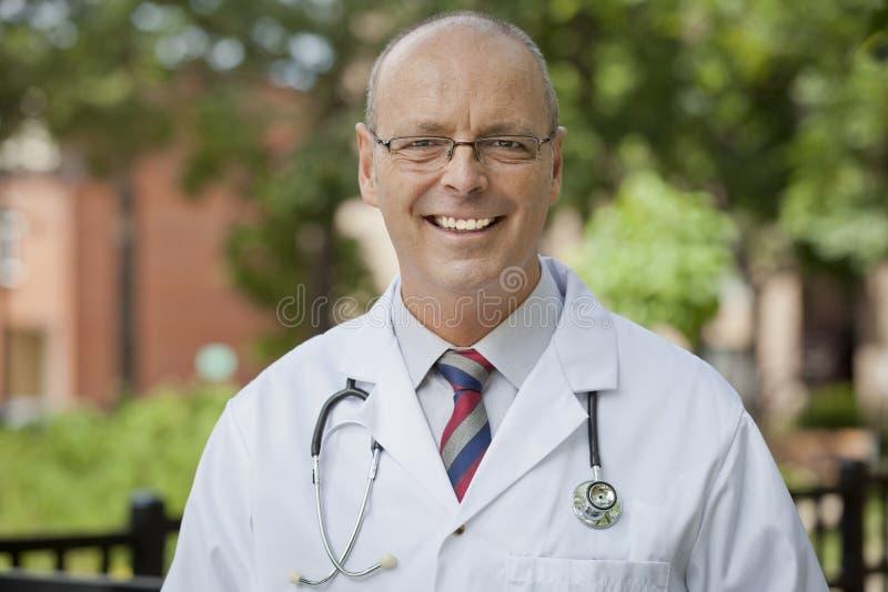 Porträt einer freundlichen Kamera Doktor-Smiling At The lizenzfreies stockbild