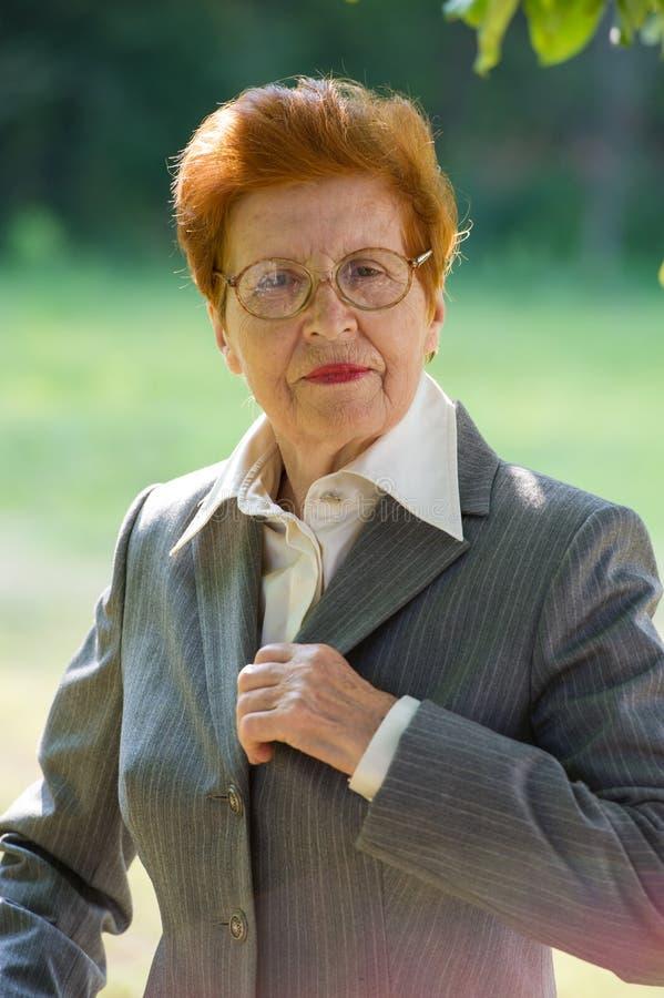 Porträt einer Geschäftsfrau alterte, eine Klage korrigierend lizenzfreies stockfoto