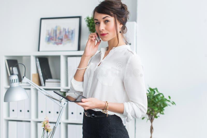 Porträt einer Geschäftsfrau, die Geschäftsanruf, Details besprechend hat und planen ihre Sitzungen unter Verwendung des Tagebuchs lizenzfreie stockfotos