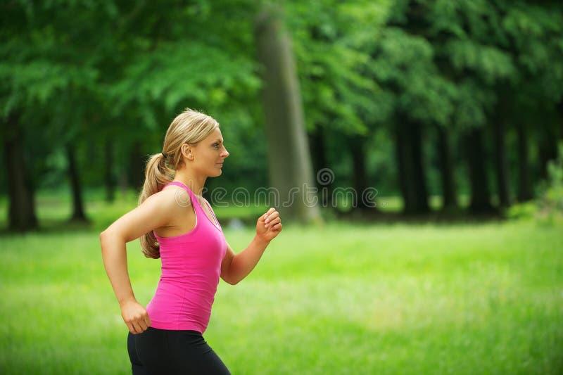 Porträt einer gesunden jungen Frau, die im Park rüttelt lizenzfreies stockbild